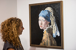 "© Licensed to London News Pictures. 04/10/2018. LONDON, UK. A gallery owner views ""Girl with the pearl ear ring (after Vermeer"" by Masha Gusova. Preview of Moniker Art Fair, taking place during Frieze Week at the Old Truman Brewery, near Brick Lane.  Now in its tenth year, the fair embraces contemporary urban art from emerging and established artists  This year, the show's theme is 'Uncensored', shedding light on social, economic and ecological issues, and is open 4 to 7 October.  Photo credit: Stephen Chung/LNP"