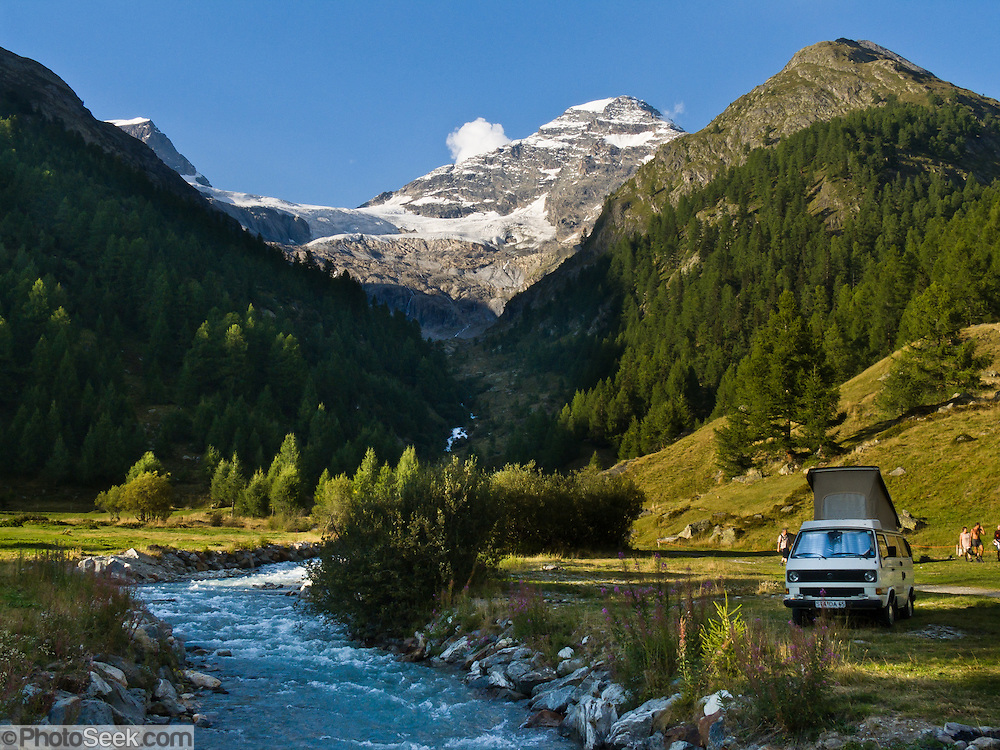 "The Breithorn (3785 meters or 12,418 feet) of Lötschental rises above a pop top camping vehicle by a river in Loetschental valley in the Valais canton of Switzerland, the Alps, Europe. UNESCO lists ""Swiss Alps Jungfrau-Aletsch"" as a World Heritage Area (2001, 2007)."