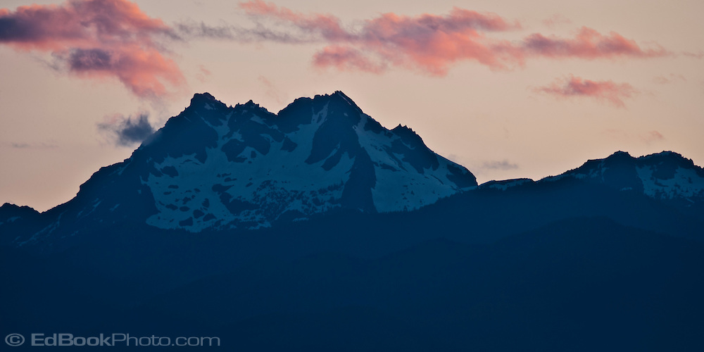The Brothers in the Olympic Mountains stands silhouetted against a twilight sky as seen from the Kitsap Peninsula in Puget Sound, Washington state, USA pan