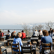 Tourists enjoy Turkish tea at an outdoor cafe in Gulhane Park overlooking the Bosphorus and situated next to the Topkapi Palace