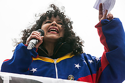 London, UK. 16th March, 2019. Carolina Graterol, wearing a jacket in the colours of the Venezuelan flag, addresses thousands of people on the March Against Racism demonstration on UN Anti-Racism Day against a background of increasing far-right activism around the world and a terror attack yesterday on two mosques in New Zealand by a far-right extremist which left 49 people dead and another 48 injured.
