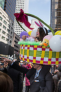 New York, NY, USA-27 March 2016. A man carries a girl surrounded by a large Easter basket on his shoulders as she throws Easter candy to the crowd on Fifth Avenue in the annual Easter Bonnet Parade and Festival.