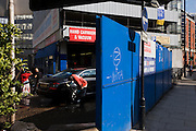 Spongeing down black car in hand car wash business and blue hoarding on street corner in Shoreditch, East London.