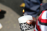 A tennager lit a candle in respect of former president Nelson Mandela out his Houghton home, Johannesburg. Scores of people were brought flowers an lit candles in memory of the fallen hero. Mandela died on the December 5 in his Houghton home.Pic. Bafana Mahlangu. Date 05/12/2013. Sowetan