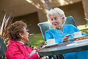 Senior Friends Having Coffee Together Outdoors on the Patio Furniture