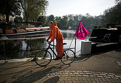 © Licensed to London News Pictures. 22/04/2019. London, UK. An Extinction Rebellion protestor cycles along the tow path in the early morning sunshine at Little Venice in London on what has been a record breaking Easter bank holiday weekend for temperatures. Photo credit: Ben Cawthra/LNP
