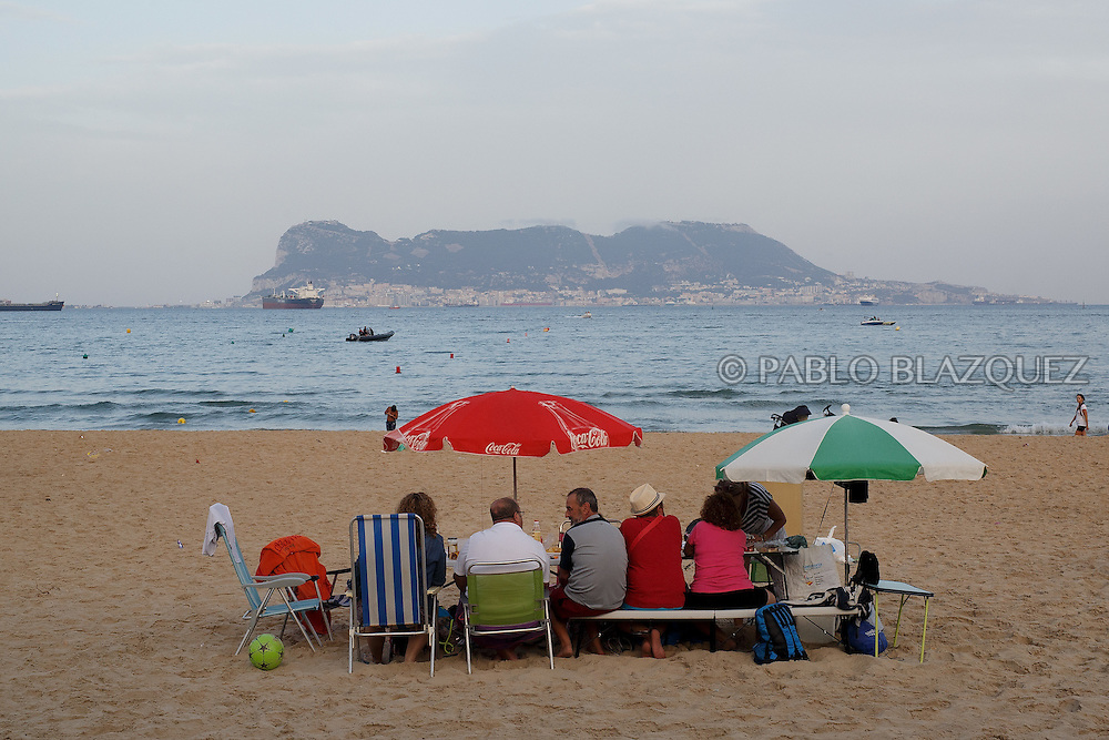 15/08/2016. Families enjoy the meals and drinks during the yearly Virgin of Palm maritime pilgrimage at El Rinconcillo beach on August 15, 2016 in Algeciras, Spain. The Our Lady of Palm maritime pilgrimage in Algeciras dates back to 1975 and takes place annually when fishermen rescue the submerged virgin from the deep sea. Worshippers amid thousands of visitors await its arrival at the Rinconcillo beach. The devotion for the Virgin of Palm comes from the seventeenth century when a ship coming from Italy docked at Algeciras port to wait out bad weather. According to legend, once the crew of the ship removed a box with an image of the Virgin from its cargo the weather turned and the sea's tides were calmed. (© Pablo Blazquez)