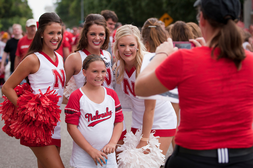 Cheerleaders pose for a picture with a fan before their Saturday Sept 7, 2013 NCAA football game in Lincoln, Neb.(Photo by/John S Peterson)
