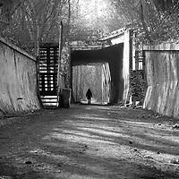 Woman walking alone under a concrete bridge