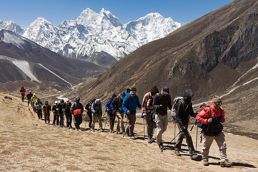 A large trekking group heading to Everest Base Camp hikes past in single file along the trail above Periche, Khumbu region, Sagarmatha National Park, Himalaya Mountains, Nepal. Kangtega and Thamserku are visible in the distance.