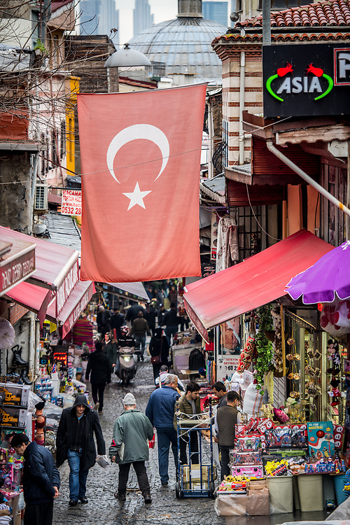 The Turkish flag hangs in between buildings in narrow street with shop selling goods below, Istanbul, Turkey