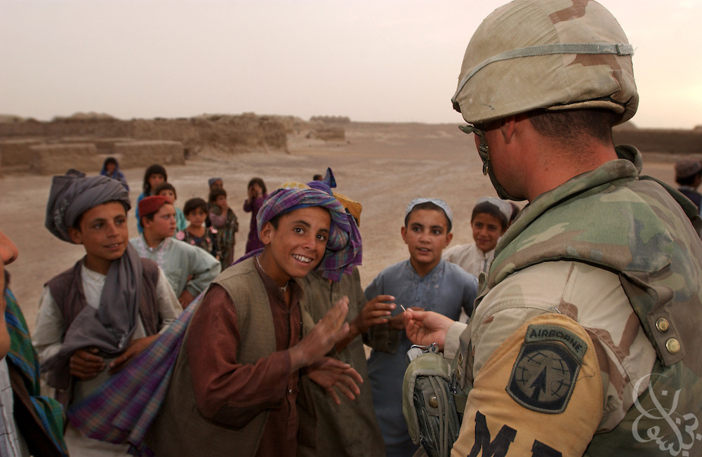 Members of the U.S. Army  3rd Platoon 108 MP company speak with local Afghan children as they patrol May 12, 2002 near the Kandahar airfield in southern Afghanistan. U.S. soldiers routinely patrol the area as part of the ongoing coalition Operation Enduring Freedom.