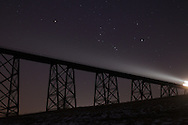 Salisbury Mills, NY - The constellation Orion rises over the Moodna Viaduct railroad bridge at twilight as a train approaches on Thursday, Jan. 14, 2010.