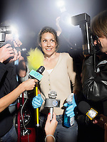 Woman with cleaning equipment being photographed by paparazzi