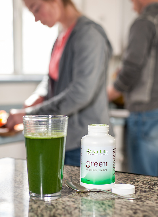 Couple preparing a healthy meal with Nu-life Green drink sitting on table in the foreground. Photo for brochures for advertising