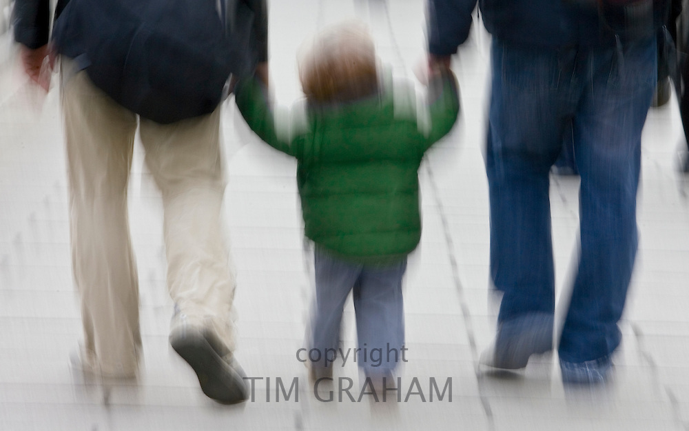 Adults hold a child's hand as they walk through London, England, United Kingdom
