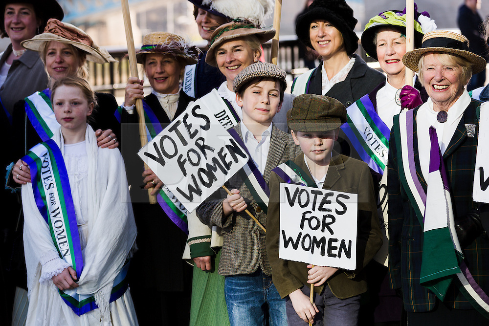 """© Licensed to London News Pictures. 08/03/2015. London, UK. Demonstrators dressed as suffragettes at the """"Walk In Her Shoes"""" event to mark International Women's Day at The Scoop amphitheatre on the south bank in London. Photo credit : Vickie Flores/LNP"""