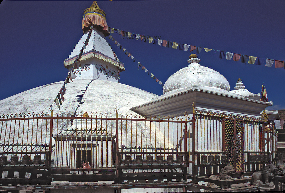 General view of the stupa, with its surrounding iron fence and border of prayer wheels. Strings of prayer flags hang from the stupa's cupola.