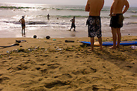 Tourists stand next to a surf board on Kuta Beach. Bali revisited January 2012.