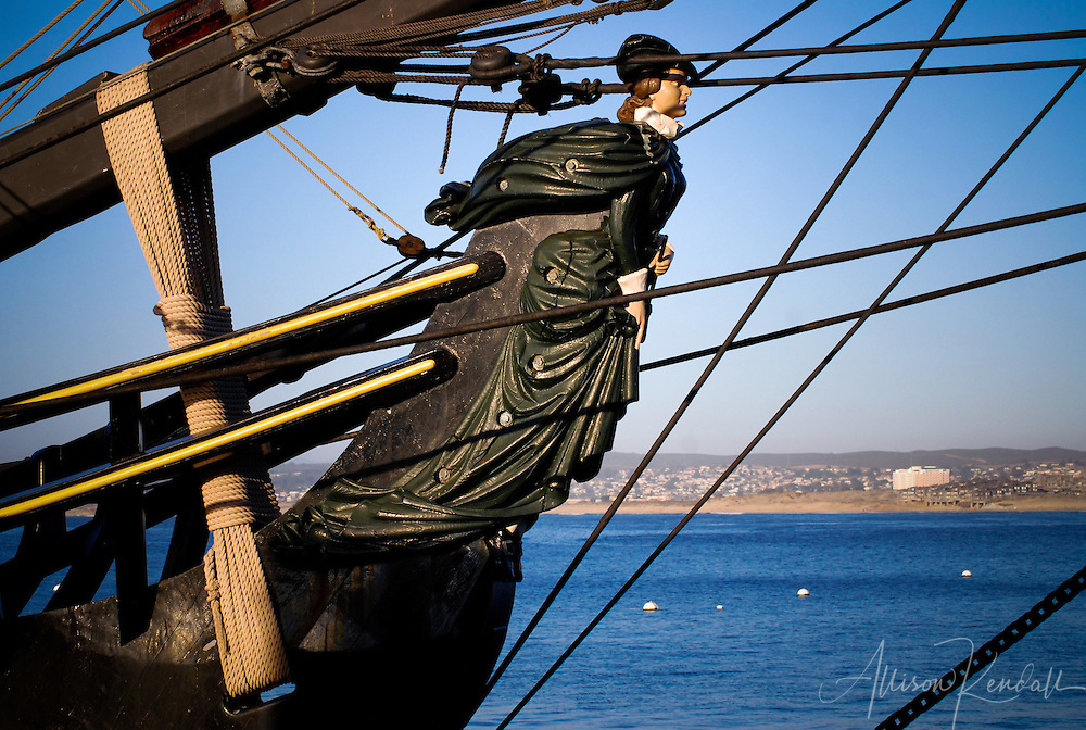 The masthead of a visiting historic sailing ship overlooks Monterey harbor and bay