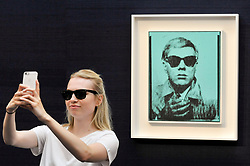 "© Licensed to London News Pictures. 23/06/2017. London, UK. A staf member takes a selfie with ""Self-Portrait"", 1963-64, by Andy Warhol (estimate GBP5-7m) at the preview of Sotheby's Contemporary Art Sale in New Bond Street.  The auction, which is dominated by Pop art, takes place on 28 June. Photo credit : Stephen Chung/LNP"