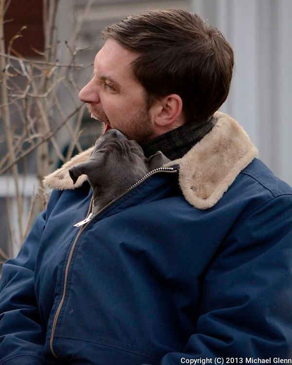 Tom Hardy gets a nibble on the chin from his four footed co-star while filming Animal Rescue