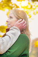 Portrait of handsome man showing affection to his wife in park with lens flare