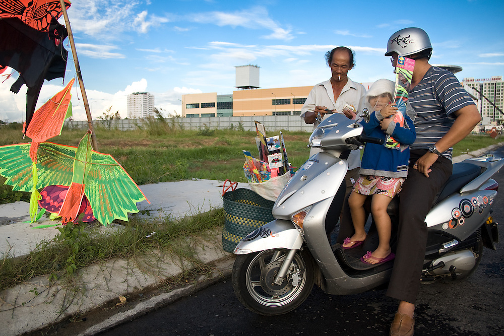 A vendor sells kites to a father and his young daughter who spend their Sunday afternoon on one of the rare open areas in Saigon to fly kites.