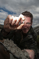 Historian Ashley Cowie finds a small flint, as he digs on a beach, on Iona, during his road trip. He is doing a seven part series for The Scottish Sun on Scotland's treasure hunts at the end of April..©Michael Schofield..