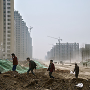 Workers -- themselves farmers made landless a few years earlier -- build a housing block to compensate farmers for their lost land in northern China. <br /> <br /> China is pushing ahead with a dramatic, history-making plan to move 100 million rural residents into towns and cities over six years &mdash; but without a clear idea of how to pay for the gargantuan undertaking or whether the farmers involved want to move.<br /> <br /> Moving farmers to urban areas is touted as a way of changing China&rsquo;s economic structure, with growth based on domestic demand for products instead of exporting them. In theory, new urbanites mean vast new opportunities for construction firms, public transportation, utilities and appliance makers, and a break from the cycle of farmers consuming only what they produce.<br /> <br /> Urbanization has already proven to be one of the most wrenching changes in China&rsquo;s 35 years of economic reforms. Land disputes rising from urbanization account for tens of thousands of protests each year.