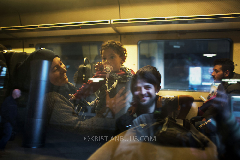 Adib, seen reflected in the train window came to to Denmark as a refugee from Syria a year ago. Now he is a volunteer at Copenhagen Airport train station helping refugges in getting to Sweden. Here he waves goodby to a family on their last leg to Swden and safety. An unprecedented number of refugees arrived from Germany in early September, most being Syrian war refugees, some from Afghanistan. Most wanted to travel on to Sweden and a number of Danish citizens created a spontanious network to assist the refugees with travel, food, clothes and psycological support.
