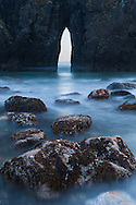The tide washes through a sea arch, allowing a view to the ocean beyond, Harris State Beach