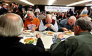 Omer C. Ahern, Jr., center, looks down at his pasta at a spagetti dinner at the Ashland American Legion where Republican 2012 presidential candidate, former Massachusetts Gov. Mitt Romney and wife Ann served out the meal, in Ashland, N.H., Wednesday, Dec. 21, 2011 . (Cheryl Senter for the New York Times)
