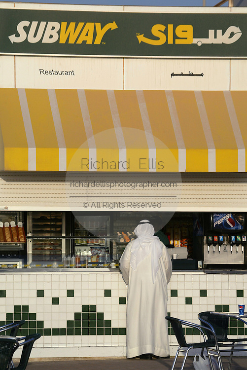 A Kuwati man in thaub, traditional clothing, orders at a Subway fastfood restaurant along the Sharq Pier in Kuwait City.