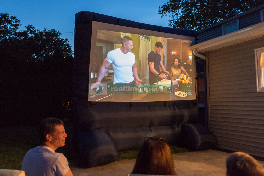 June 11, 2017 - Merrick, New York, United States - At bottom left, CHRIS EDOM, 'American Grit' TV contestant, 48, of Merrick, hosts backyard Viewing Party for Season 2 premiere. The Fox network reality television series show projeted on large screen, with (L-R) JOHN CENE, and 2 of his Cadre members, JOHN BURKE and RIKI LONG. Edom was last of 16 contestants picked for a team that episode. (Credit Image: © Ann Parry via ZUMA Wire)