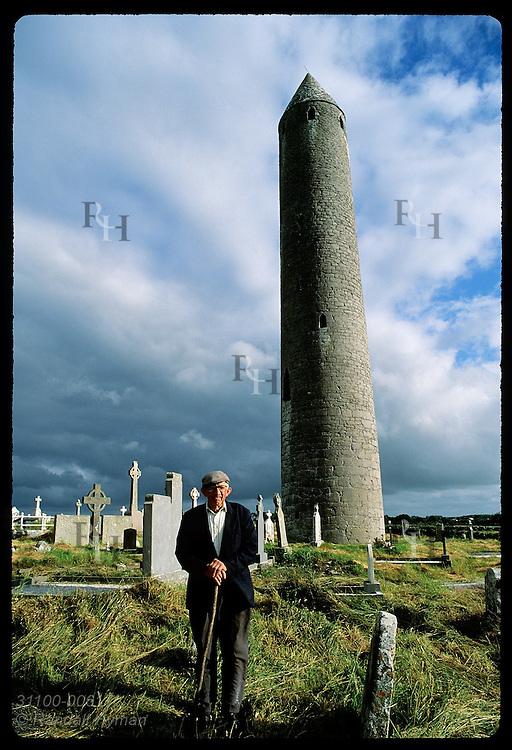 Caretaker Colman Finnegan with rake by Kilmacduagh round tower, St Colman monastery site; Gort. Ireland