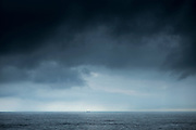 Dramatic scene - tanker under dark grey looming clouds in The Bay of Biscay north of Santander, the Atlantic Ocean, Spain