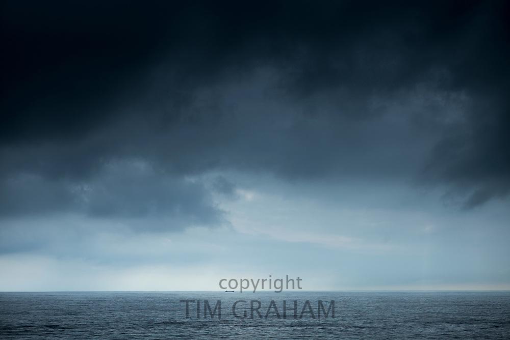 Dramatic scene - tanker under dark grey looming clouds in The Bay of Biscay north of Santander, the Atlantic Ocean, Spain