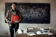 Lei Shui Xiang, headmaster of Guan Shan (Gansu) primary school, holding awards. Devoted to the children, covered with academic honors, his monthly income of RMB 150 hasn't changed in 25 years, in spite of repeated request to have his status changed.