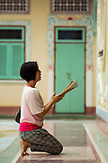 06 JUNE 2013 - BANGKOK, THAILAND:   Women pray with incense at Wat Bhoman Khunaram. Wat Bhoman Khunaram on Sathu Pradit Road in Bangkok, is considered the most beautiful Chinese temple in Thailand. The temple was built in a blend of Thai, Chinese and Tibetan styles. It was built in the 1959 and is a Mahayana Buddhist temple (most Thais are Theravada Buddihists). There is a monastery on the temple grounds and many boys go to the temple to become monks and learn Chinese Buddhist rituals and Chinese language.      PHOTO BY JACK KURTZ