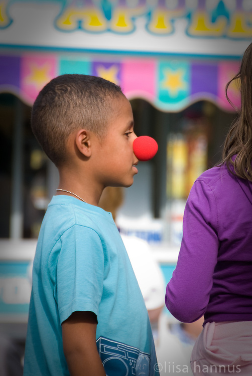 A young boy wears a red clown nose while on a summer visit to  the Pacific National Exhibition in Vancouver, British Columbia