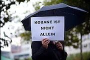 Frankfurt am Main | 08 Oct 2014<br /> <br /> Am Mittwoch (08.10.2014) nahmen an der Konstablerwache in der Innenstadt von Frankfurt am Main etwa 100 Menschen an einer Kundgebung f&uuml;r Solidarit&auml;t mit der von IS (ISIS, ISIL, Islamischer Staat) angegriffenen Stadt Kobane (auch: Ain al-Arab) teil. Die kundgebung verlief friedlich, es kam nur zu einer kleinen St&ouml;rung durch einen jungen Moslem, der sich durch einen Redebeitrag in seinem Glauben beleidigt f&uuml;hlte.<br /> Hier: Eine Frau mit einem Plakat mit der Aufschrift &quot;Kobane ist nicht allein&quot;.<br /> <br /> &copy;peter-juelich.com<br /> <br /> [No Model Release | No Property Release]