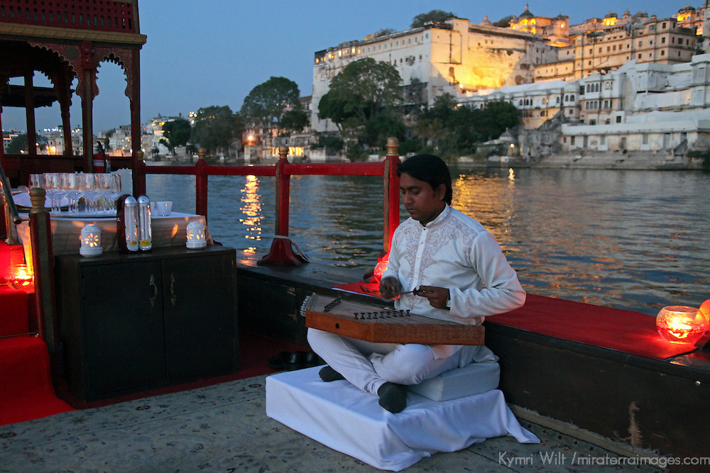 Asia, India, Udaipur. Musician plays aboard gangaur cruise on Lake Pichola, from Taj Lake Palace Hotel.
