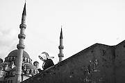 A young womand wals down the stairs at Galata bridge, in Istanbul, with the minarets of New Mosque on the background