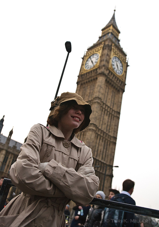 A young girl stands outside of Parliament and Big Ben clocktower, London, England.