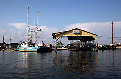 26 May 2010. Barataria Bay to Grand Isle, Jefferson/Lafourche Parish, Louisiana. <br /> Fishing boats tied up at Jean Lafitte just south of New Orleans. The region is strategically vital to the American oil and gas industry and a major player in America's seafood industry. BP's catastrophic oil spill continues to spew a black tide of death which continues to encroach upon everything in the region. The economic impact is devastating with shrimp boats tied up, vacation rentals and charter boat fishing trips are cancelled. The only real business is cleaning up big oil's disasterous screw up. Oil from the Deepwater Horizon catastrophe is evading booms laid out to stop it thanks in part to the dispersants which means the oil travels at every depth of the Gulf and washes ashore wherever the current carries it. <br /> Photo credit; Charlie Varley<br /> www.varleypix.com