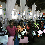 Mothers wait with their babies at the crowded pediatric ward at Mulago hospital in Kampala.