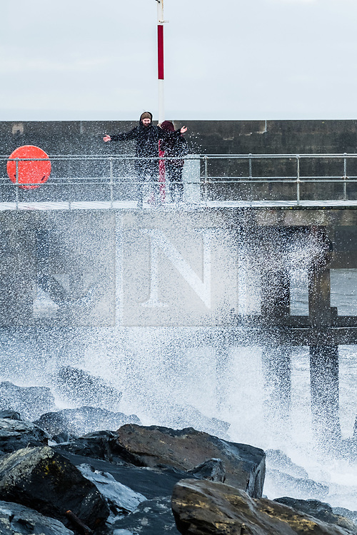© Licensed to London News Pictures<br /> Aberystwyth, UK. 26/10/2018. A couple get splashed by the waves at the harbour as bitterly cold northerly winds, with stinging rain and sleet,  blow over Aberystwyth on the Cardigan Bay coast of west Wales as the weather turns decidedly wintry. <br /> Photo credit : Keith Morris/ LNP
