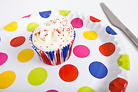 Cupcake in multicolored plate with polka dots against white background