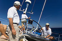 Sailors at helm of sailboat